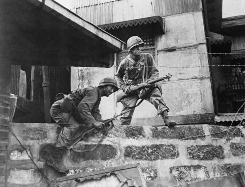 Feb. 13, 1945: Two Yank Infantrymen of the hard fighting 37th American division, climb through some Japanese barbed wire during street fighting in Manila in the Philippines. (AP Photo)